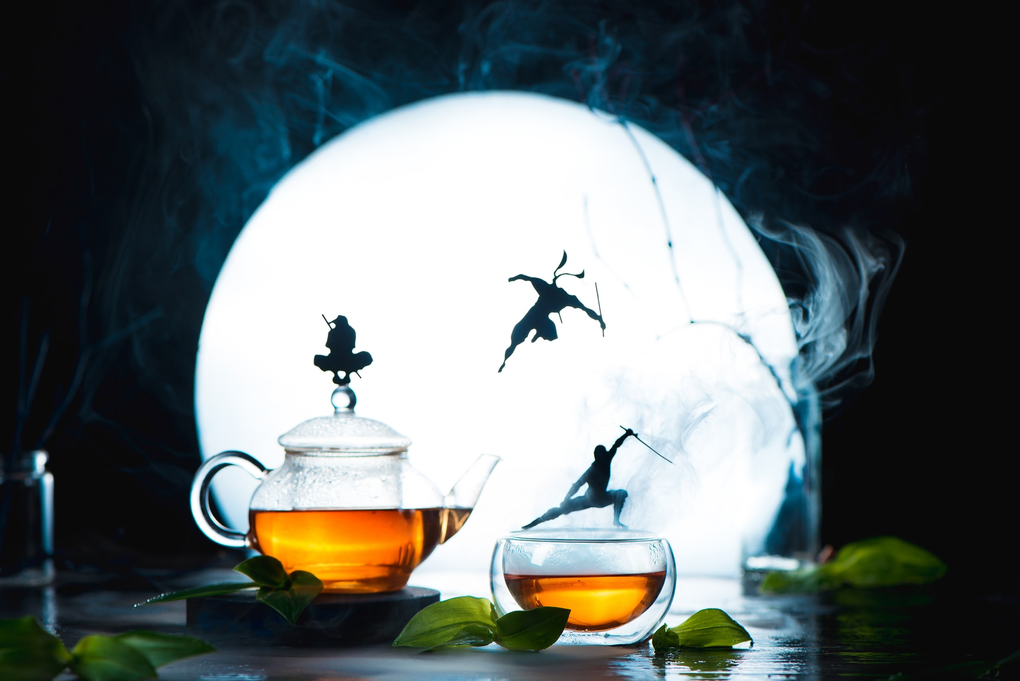 Conceptual tea photography with ninja silhouettes on tea cups. Creative hot drink header with full