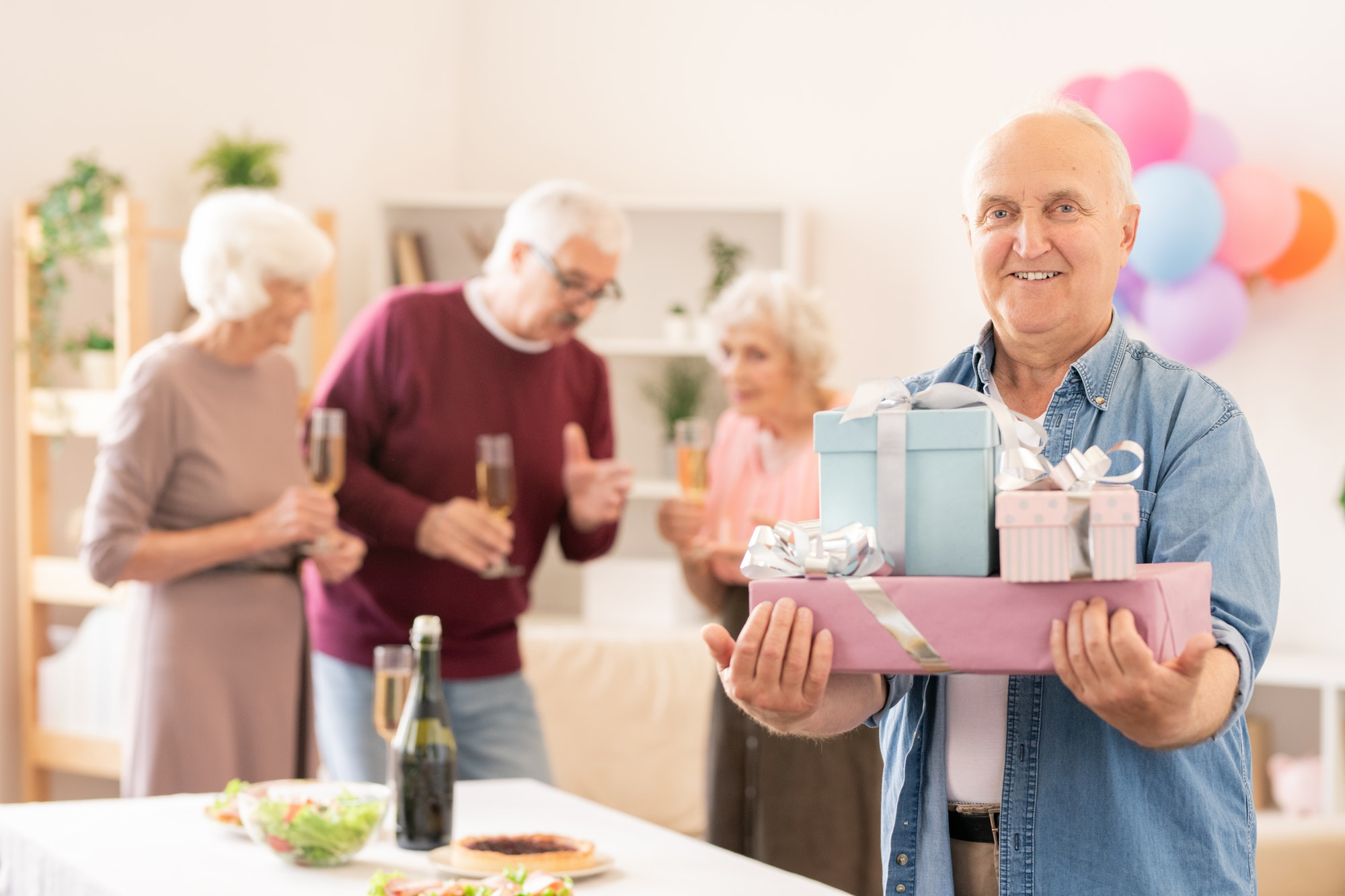 Senior smiling man with several packed gifts